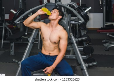 Asian man has muscle exercise in the gym.And Asian handsome muscles are tired, so drink Electrolyte drink.