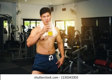 Asian man has muscle exercise in the gym.And Asian handsome muscles are tired, so drink Electrolyte drink.Exercise in gym concept.