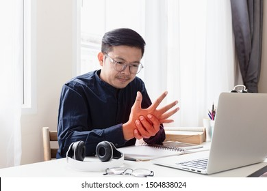 An Asian man has pain in his wrist for working hard on his desk.