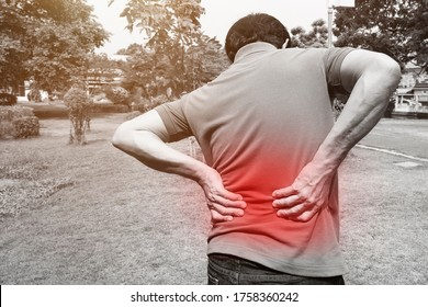 Asian man has suffering from accident back pain at outdoor./People healthcare,Sepia effect and red spot effect at pain area.