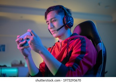 asian man have live stream and playing mobile game on the smartphone at home