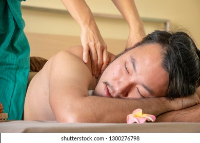 """A Asian man is having Thai massage .Thai massage or """"Thai yoga massage"""" is a traditional healing system combining acupressure, Indian Ayurvedic principles, and assisted yoga postures."""