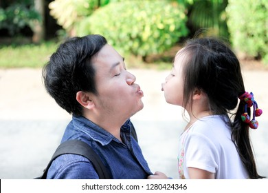 asian man and his daughter show pucker lips, he kiss asian children on nature background