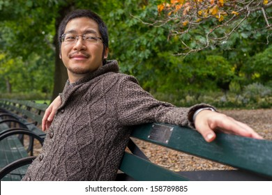 an asian man in his twenties relaxing on a bench in a park