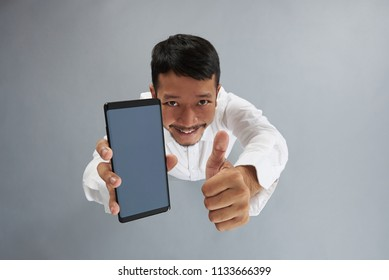 Asian man hold smartphone and show thumb up isolated on gray background above top view