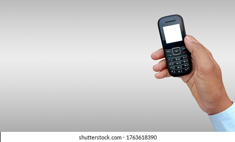 Asian man holding feature or keypad phone in hand