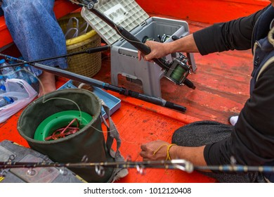 asian man holding a fishing rod with fishing tool box on the fisherman boat