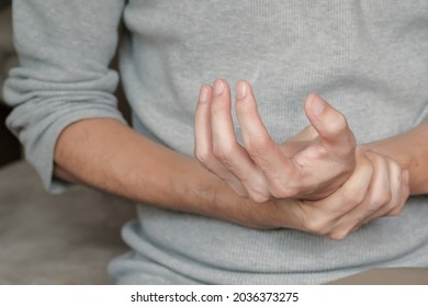 Asian man holding hand with muscle weakness, numbness and paralysis symptoms after vaccination. Guillain Barre syndrome rare cause by autoimmune disorder concept. Selective focus.
