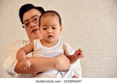Asian man holding his baby with love.Smart dad with lovely son.Happy family in house concept.Parent with little boy.Love and relationship idea with copy space.Think for the future