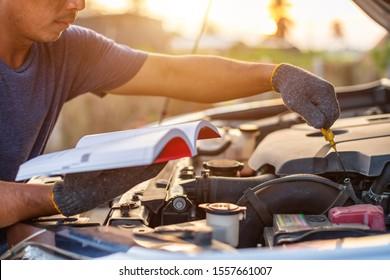 Asiatischer Mann, der die Gebrauchsanweisung oder Bedienungsanleitung für das Prüfen oder Befestigen der Motor des modernen Autos hält und liest. Fahrzeugwartung oder -dienst vor dem Fahrkonzept