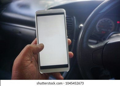 Asian man holding smartphone while driving a car. A good concept picture of man using phone while driving, for apps based services, sms, online banking, travel and others.