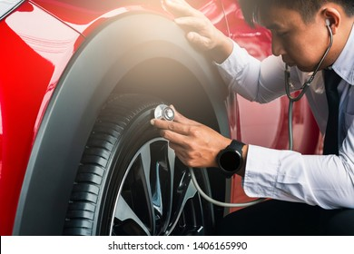 Asian man holding stethoscope with inspection car rubber tires.Close up holding stethoscope for car tyre pressure measurement for automotive, automobile image