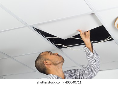 Asian man install suspended ceiling in house