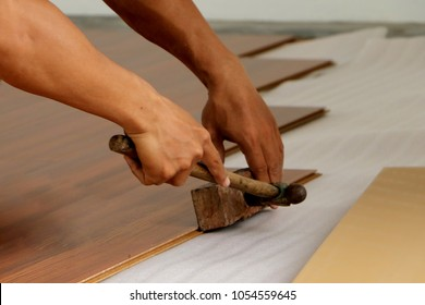Asian man installing new laminate flooring. Focus on Hand holding a hammer