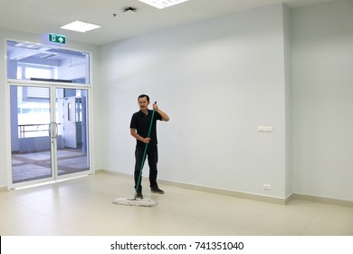 Asian man janitor mopping floor in hallway office building. Commercial cleaning services company concept.