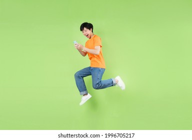 Asian man jumping and holding smartphone , isolated on green