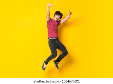 Asian man jumping over isolated yellow wall