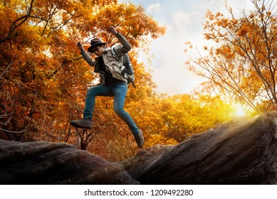 Asian Man jumping over rocky in autumn forest with sunlight background. Adventure Travel, Freedom Travel, Success, Risk and Challenge of People.