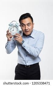 Asian man listening to an alarm clock