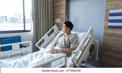 Asian man look view out of window , the pain in the knee after surgery for fixing knee and for healing and recovery ACL injuriesin on rehabilitation room in the hospital
