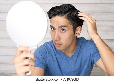 Asian man looking at his hair in mirror