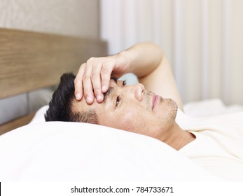 asian man lying on bed eyes open hand on forehead looking tired depressed or frustrated.