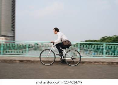 Asian man mad riding bicycle in urban city commuting with speed and hipster trendy transportation