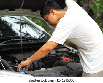 Asian man maintenance engine of car,Man white shirt found trouble in engine of car in his house and find the problem interior the car for repair