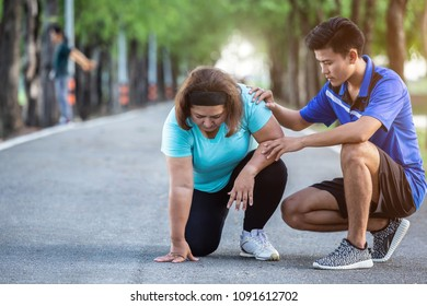 Asian man make encouragement to fat woman who tired and sitting on ground