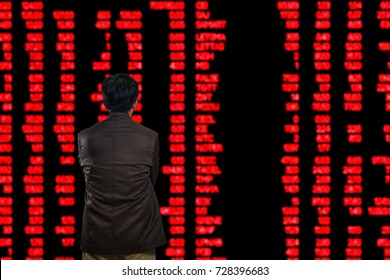Asian Man or Male Looking at Stock Trading data on Display Board at Stock Exchange Market as Business financial investment concept. The Market trend is decrease or Down as show in red Figure.