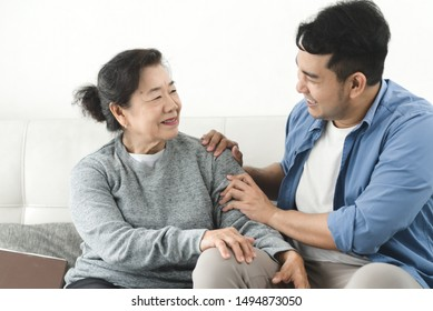 Asian man massage his mother at home, lifestyle concept.