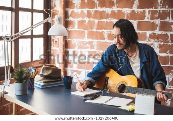 Asian man musician writing song with guitar