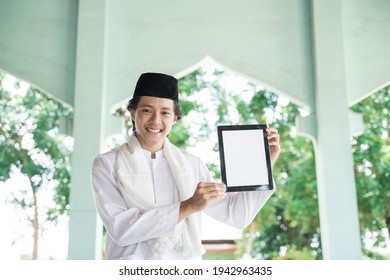 asian man muslim smiling holding blank tablet