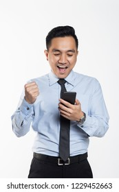 Asian man in office wear looking at his handphone with being success expression