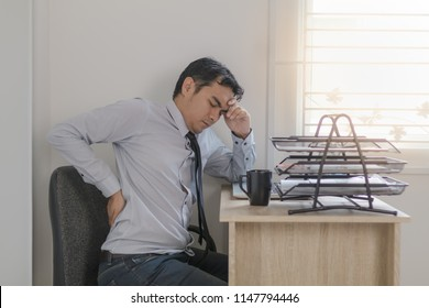 Asian man officer have back pain while sitting on a chair at his desk