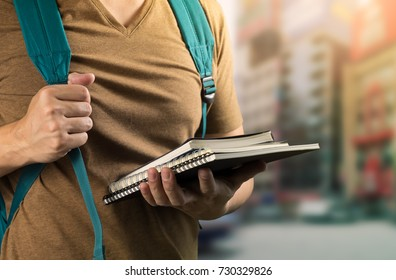asian man on brown t-shirt holding study book and card green bag to ready to go to school or university on blur city background