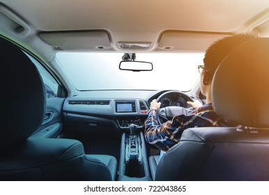 Asian man on hipster shirt hand driving a car with isolated windshield front for driving concept.