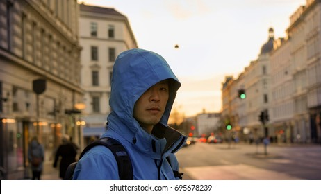 Asian man with outdoor jacket, sporty look with sunset European architecture background