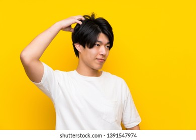 Asian man over isolated yellow wall having doubts while scratching head