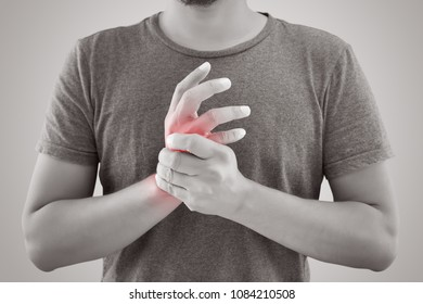 Asian man with pain in wrist against gray background. People suffering from chronic joint rheumatism. Body & Health concept