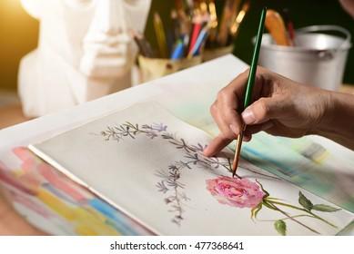 Asian man painting brush watercolors on paper.