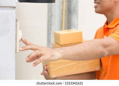 Asian man with parcel box ringing customers doorbell. Delivery man in orange uniform ringing the bell. Home delivery courier service and shipment concept