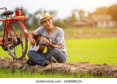 Asian man playing guitar at the green rice field in the sunset time. Countryside of Thailand