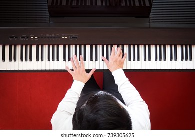 Asian man playing piano by two hands. Top view with red floor background. Favorite music instrument for learning basic of rhythm and music skill. Art background.