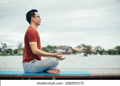 Asian man playing with a yoga school at yoga class in early morning. Lifestyle and healty concept.