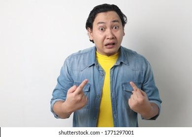 Asiatischer Mann, der sich mit unglücklichem, verärgerten Ausdruck zeigt, als ob er verwirrt wäre, beschuldigt zu werden, und fragte, wer? Ich?