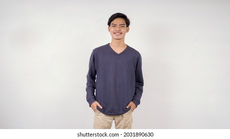 Asian man posing casually with his hands in his pockets facing the front isolated on white background