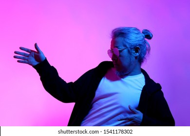 The Asian man posing on the white background with the gel color light.