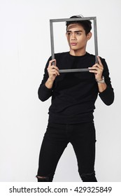 asian man posing while holding an empty photo frame