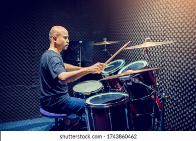 Asian man put black t-shirt to playing the drum set with wooden drumsticks in music room , the concept of musical instrument.